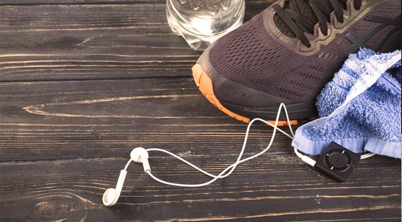 Chaussures de sports, serviette, bouteille d'eau et Ipod touch sur une table noire
