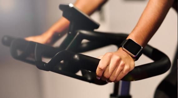 Femme avec une montre connecté sur un vélo d'appartement