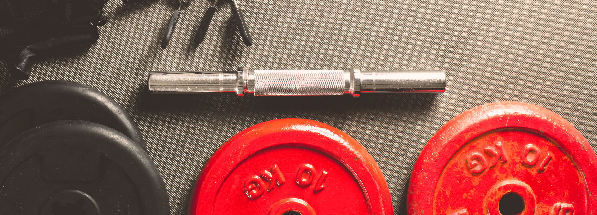 Lot de deux poids rouges de 10 kilos et leur barre d'haltère