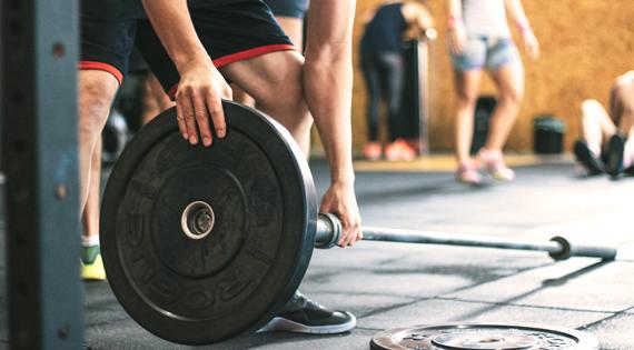 Homme en train de monter une barre de musculation