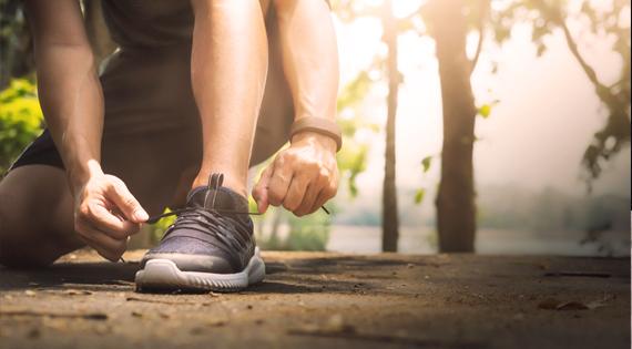 Homme faisant du running en train de lacer ses chaussures