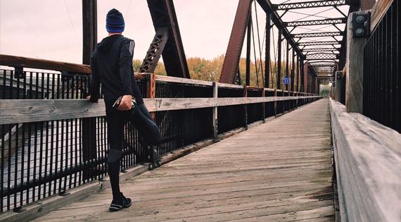 Homme en tenue de sport s'étirant sur un pont en bois